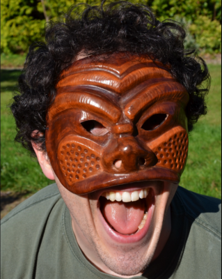 this is an image of a man wearing a commedia mask - it is brown, intricately carved wood that covers the face down to the nose and cheeks. It has holes for the eyes and little breathing holes for the nose.