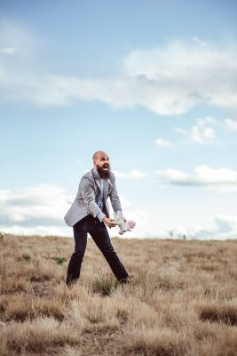 This is a silly and playful photo of strother gaines. He is in a dessert with a vast open field. He's standing in dried grasses, wearing a nice suit, throwing a stuffed unicorn.